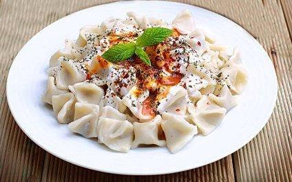 世界美食大师-Plates of traditional Turkish food. Manti with tomato sauce