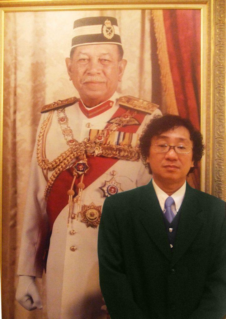 廖城兰摄於皇宫最高统治者肖像旁